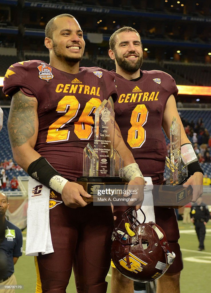 Shamari Benton #26 and Ryan Radcliff #8 of the Central Michigan University Chippewas stand with their trophies after the victory against the Western Kentucky University Hilltoppers in the Little Caesars Pizza Bowl at Ford Field on December 26, 2012 in Detroit, Michigan. The Chippewas defeated the Hilltoppers 24-21.
