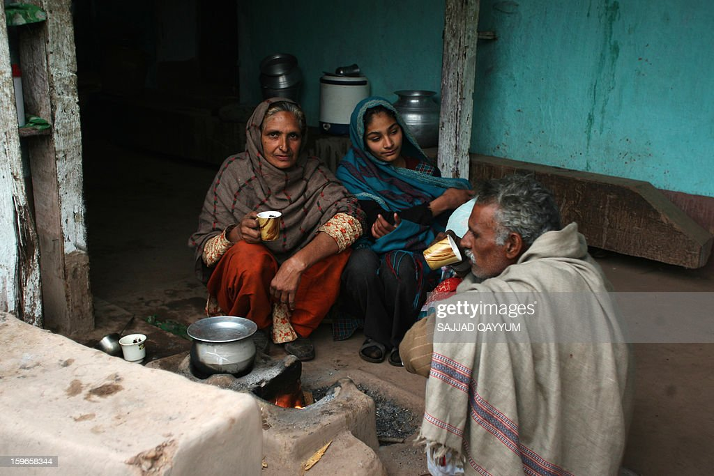 Shameer Begum (L), a 55-year-old widow, drinks tea with neighbours at her home in Parla Mohrra on January 17, 2013. On both sides of the de facto border in Kashmir, villagers living on one of the world's most dangerous flashpoints have special reason to fear the return of tension between India and Pakistan. AFP PHOTO/Sajjad QAYYUM