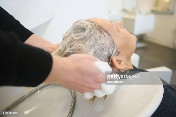 Shampooing hair in salon basin