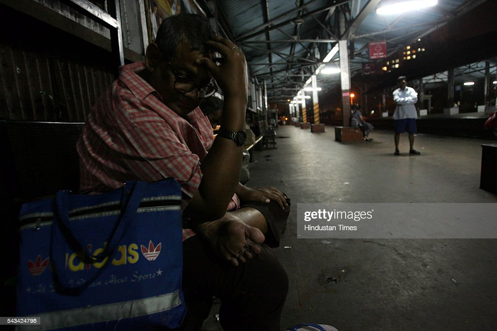 A Shamsuddin, a manager in a hotel at Thane waits for the train at Sion station on July 31, 2005 in Mumbai, India. in Mumbai, India. evening. Train services are disrupted again due to heavy rain.