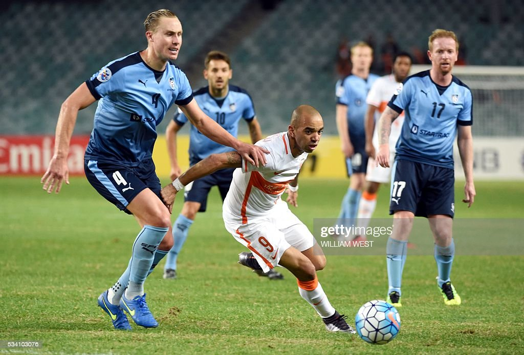 Shandong Luneng player Diego Tardelli Martins (C) evades the tackle of Sydney FC player Zac Anderson (L) as David Carney (R) looks on during their AFC Champions League round of 16 second leg football match in Sydney on May 25, 2016. / AFP / WILLIAM