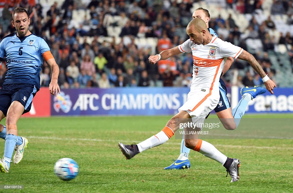 Shandong Luneng player Diego Tardelli Martins (R) shoots on goal as Sydney FC player Rob Stamolziev (L) looks on during their AFC Champions League round of 16 second leg football match in Sydney on May 25, 2016. / AFP / WILLIAM