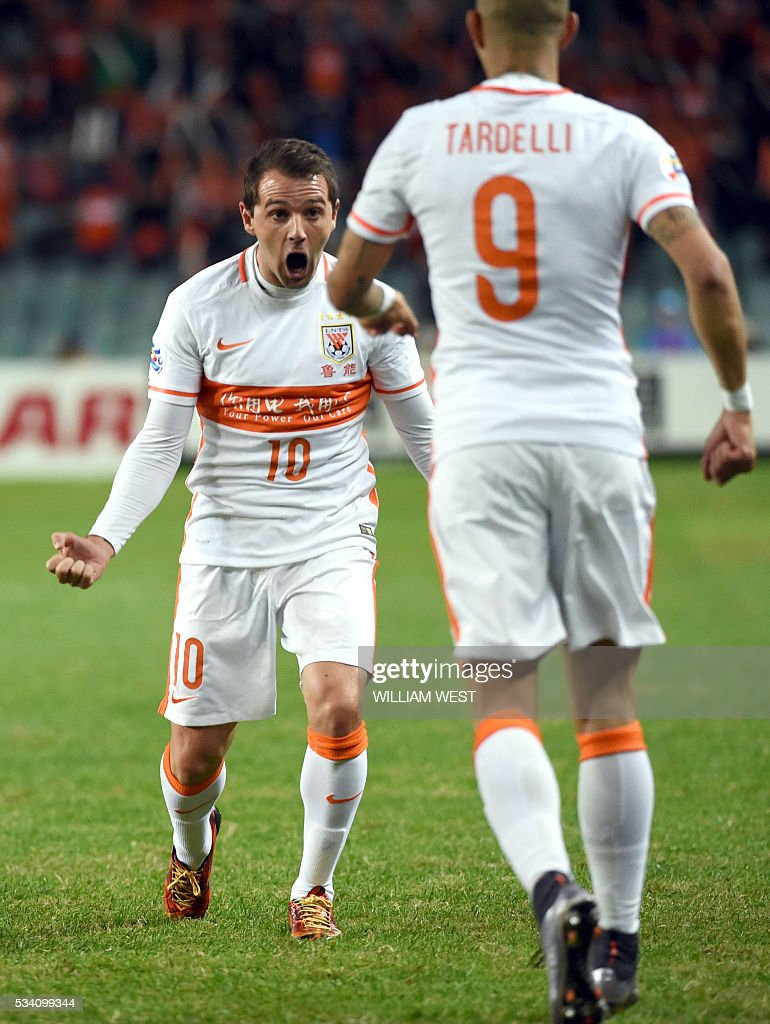 Shandong Luneng player Walter Montillo (L) celebrates with teammate Diego Tardelli Martens (R) after scoring against Sydney FC during their AFC Champions League round of 16 second leg football match in Sydney on May 25, 2016. / AFP / WILLIAM