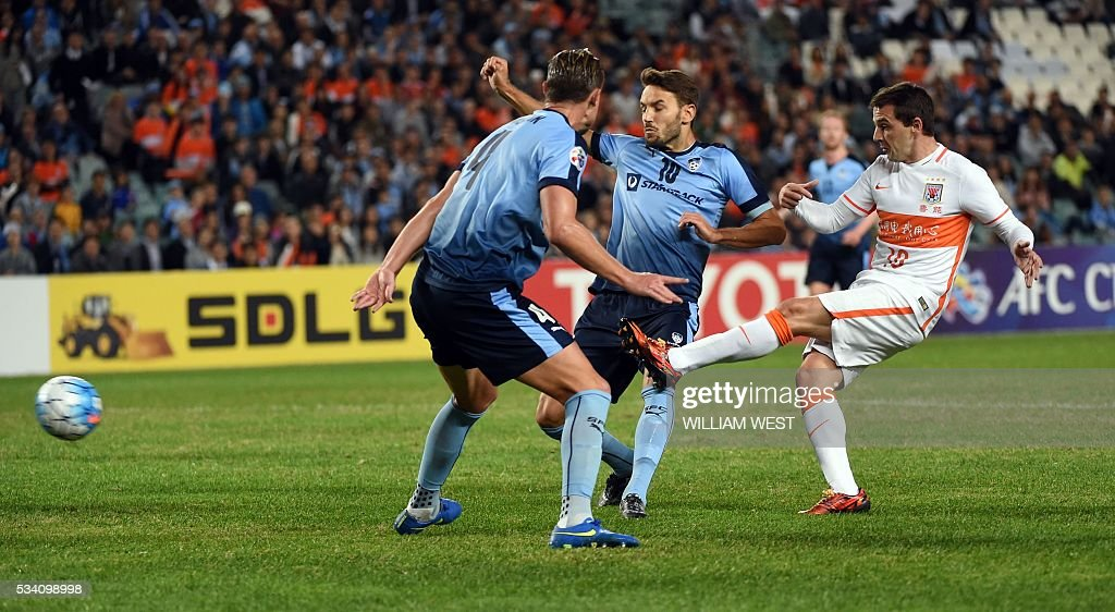 Shandong Luneng player Walter Montillo (R) scores as Sydney FC players Milos Ninkovic (C) and Zac Anderson (L) look on during their AFC Champions League round of 16 second leg football match in Sydney on May 25, 2016. / AFP / WILLIAM