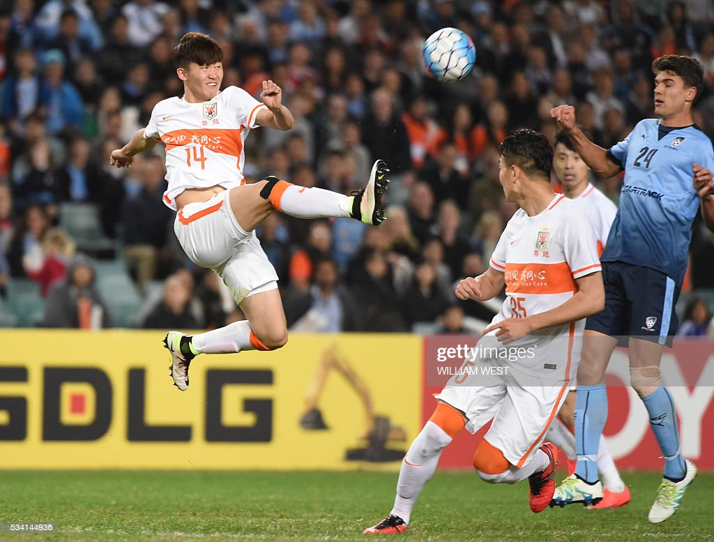Shandong Luneng player Wang Tong (L) clears a ball away from the Sydney FC attack during their AFC Champions League round of 16 second leg football match in Sydney on May 25, 2016. / AFP / WILLIAM