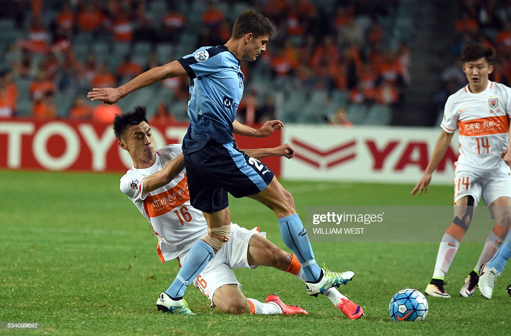 Shandong Luneng player Zheng Zheng (L) tackles Sydney FC player George Blackwood (C) during their AFC Champions League round of 16 second leg football match in Sydney on May 25, 2016. / AFP / WILLIAM