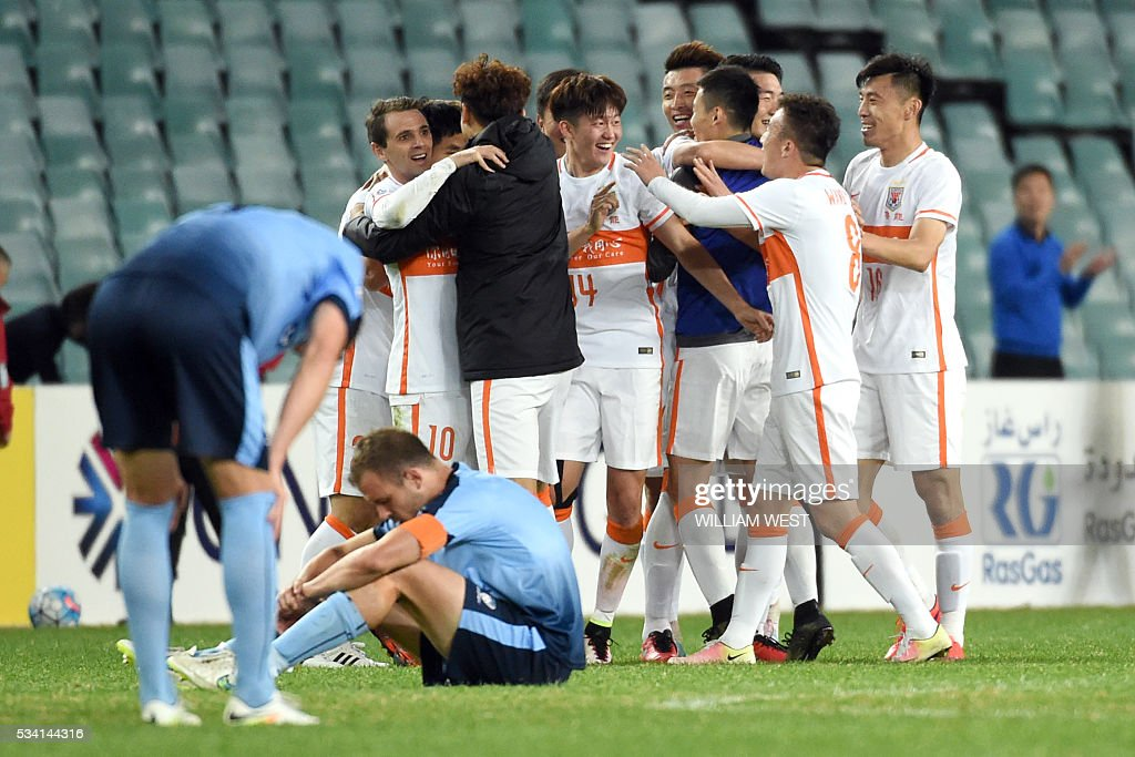 Shandong Luneng players celebrate after the final whistle while Sydney FC players react during their AFC Champions League round of 16 second leg football match in Sydney on May 25, 2016. / AFP / WILLIAM