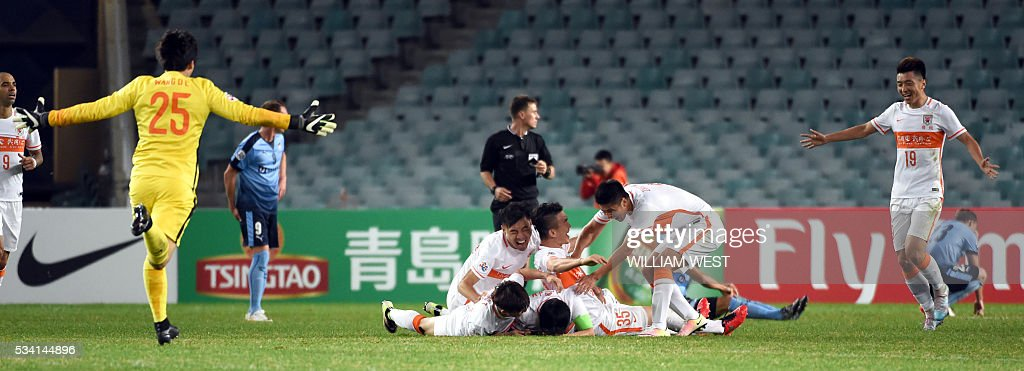 Shandong Luneng players celebrate celebrate the team's second goal against Sydney FC during their AFC Champions League round of 16 second leg football match in Sydney on May 25, 2016. / AFP / WILLIAM