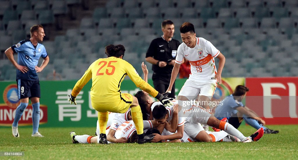 Shandong Luneng players celebrate the team's second goal against Sydney FC during their AFC Champions League round of 16 second leg football match in Sydney on May 25, 2016. / AFP / WILLIAM