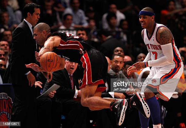 Shane Battier of the Miami Heat dives in the air to keep the ball from going out of bounds in the second half against Carmelo Anthony of the New York...