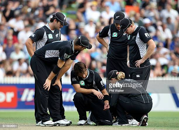 Shane Bond of New Zealand holds his hand in pain after getting hit by the ball during the One Day International match between New Zealand and...