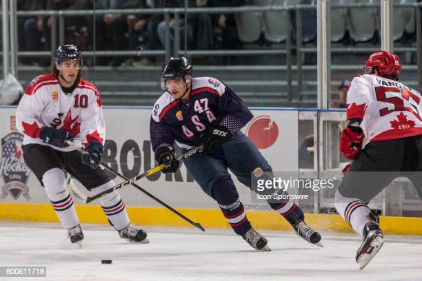 Shane Brennan of Team USA controls the puck in front of Steve McParland of Team Canada and Davis Vandane of Team Canada during the Melbourne Game of...