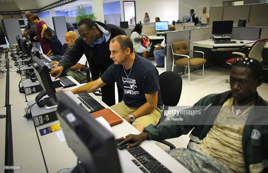 Shane Budde is helped by South Florida Workforce customer service representative, Troy Rawlins as he looks for job opportunities on the computer at the South Florida Workforce center February 1, 2013 in Miami, Florida. The Labor Department announced that U.S. employers added 157,000 jobs in January compared with a revised 196,000 jobs the previous month and the unemployment rate was little changed at 7.9 percent. (Photo by Joe Raedle/Getty Images))