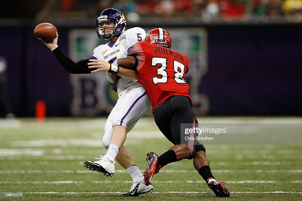 Shane Carden #5 of the East Carolina Pirates is tackled by Trae Johnson #38 of the Louisiana-Lafayette Ragin Cajuns during the R+L Carriers New Orleans Bow at the Mercedes-Benz Superdome on December 22, 2012 in New Orleans, Louisiana.