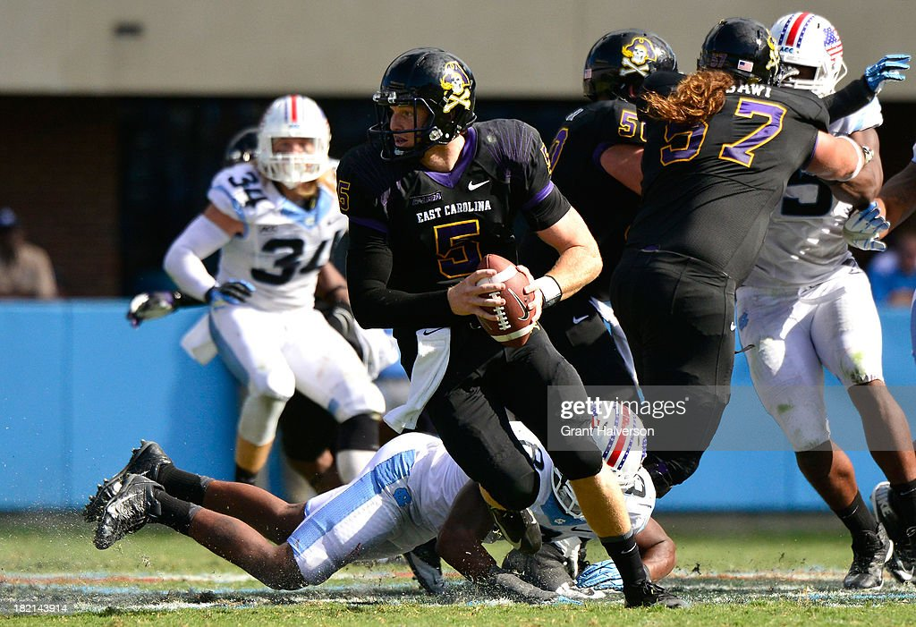 Shane Carden #5 of the East Carolina Pirates rolls out under pressure the North Carolina Tar Heels during play at Kenan Stadium on September 28, 2013 in Chapel Hill, North Carolina. East Carolina won 55-31.
