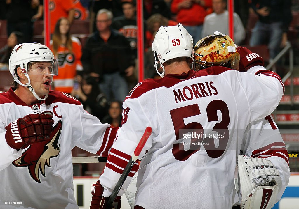 <a gi-track='captionPersonalityLinkClicked' href=/galleries/search?phrase=Shane+Doan&family=editorial&specificpeople=201614 ng-click='$event.stopPropagation()'>Shane Doan</a> #19, <a gi-track='captionPersonalityLinkClicked' href=/galleries/search?phrase=Derek+Morris&family=editorial&specificpeople=204188 ng-click='$event.stopPropagation()'>Derek Morris</a> #53, and <a gi-track='captionPersonalityLinkClicked' href=/galleries/search?phrase=Thomas+Greiss&family=editorial&specificpeople=695275 ng-click='$event.stopPropagation()'>Thomas Greiss</a> #1 of the Phoenix Coyotes celebrate after defeating the Philadelphia Flyers 2-1 on October 11, 2013 at the Wells Fargo Center in Philadelphia, Pennsylvania.