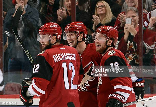 Shane Doan of the Arizona Coyotes celebrates with teammates Max Domi and Brad Richardson after his first period goal against the Winnipeg Jets at...