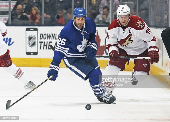 Shane Doan of the Arizona Coyotes chases after a loose puck against Daniel Winnik of the Toronto Maple Leafs during an NHL game at the Air Canada...