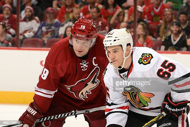 Shane Doan of the Arizona Coyotes gets ready during a faceoff against Andrew Shaw of the Chicago Blackhawks at Gila River Arena on March 12 2015 in...