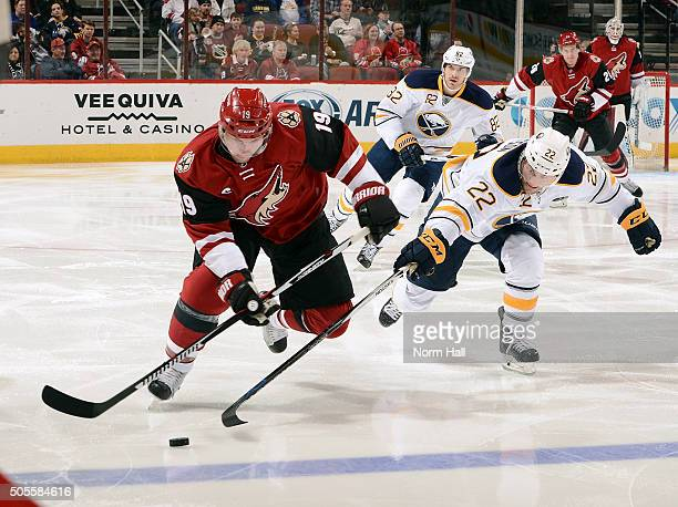 Shane Doan of the Arizona Coyotes skates with the puck as Johan Larsson of the Buffalo Sabres defends during the second period at Gila River Arena on...