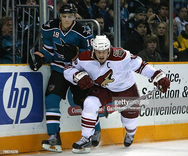 Shane Doan of the Phoenix Coyotes battles along the boards with Matt Carle of the San Jose Sharks during the NHL game at HP Pavilion on December 20...