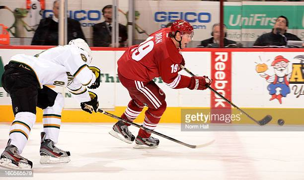 Shane Doan of the Phoenix Coyotes skates the puck up ice past Tomas Vincour of the Dallas Stars during the second period at Jobingcom Arena on...