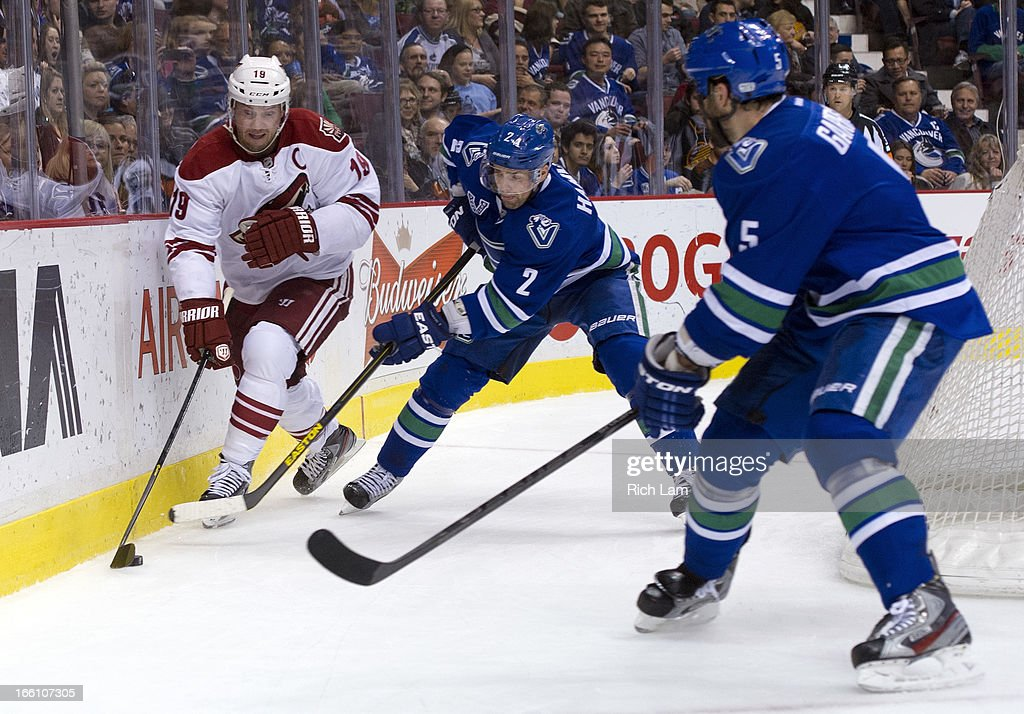 Shane Doan #19 of the Phoenix Coyotes tries to break away from Dan Hamhuis #2 of the Vancouver Canucks while Jason Garrison #5 looks on during the second period in NHL action on April 08, 2013 at Rogers Arena in Vancouver, British Columbia, Canada.
