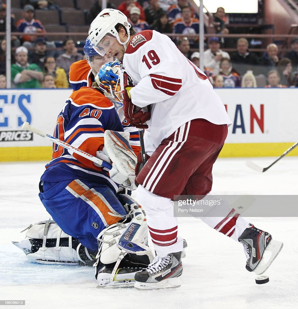 <a gi-track='captionPersonalityLinkClicked' href=/galleries/search?phrase=Shane+Doan&family=editorial&specificpeople=201614 ng-click='$event.stopPropagation()'>Shane Doan</a> #19 of the Phoenix Coyotes tries to knock in a rebound against <a gi-track='captionPersonalityLinkClicked' href=/galleries/search?phrase=Devan+Dubnyk&family=editorial&specificpeople=2089794 ng-click='$event.stopPropagation()'>Devan Dubnyk</a> #40 of the Edmonton Oilers at Rexall Place on April 10, 2013 in Edmonton, Canada.