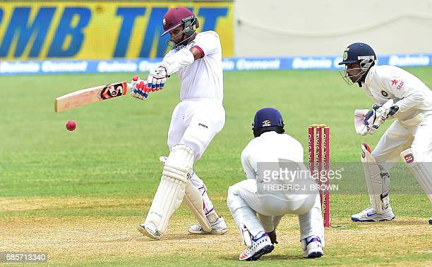 Shane Dowrich of the West Indies connects for a hit off a delivery from Ravichandran Ashwin of India as Cheteshwar Pujara and wicket keeper...