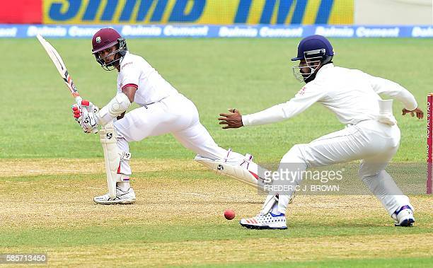 Shane Dowrich of the West Indies connects for a hit past Cheteshwar Pujara of India off a delivery from Ravichandran Ashwin on day five of their...