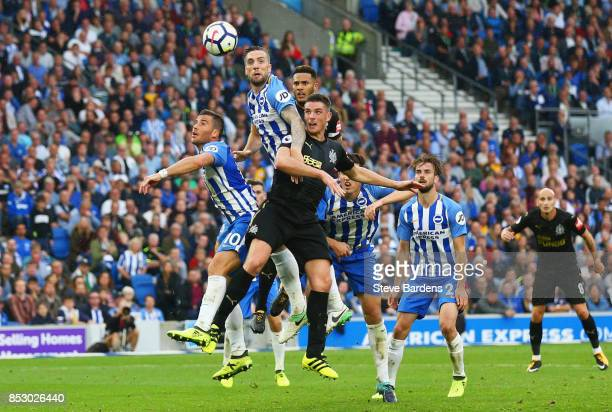 Shane Duffy and Tomer Hemed of Brighton and Hove Albion jump with Ciaran Clark of Newcastle United during the Premier League match between Brighton...