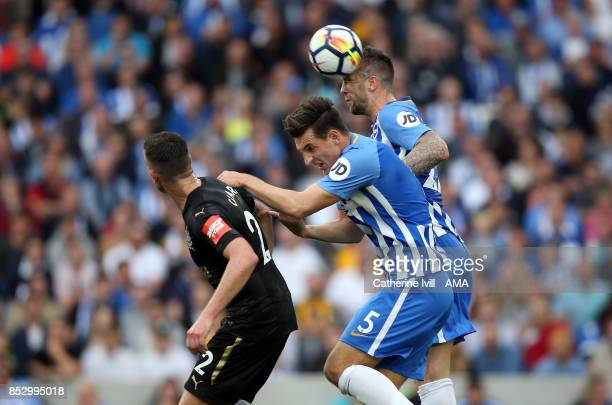 Shane Duffy of Brighton and Hove Albion gets up before Ciaran Clark of Newcastle United and Lewis Dunk of Brighton and Hove Albion during the Premier...