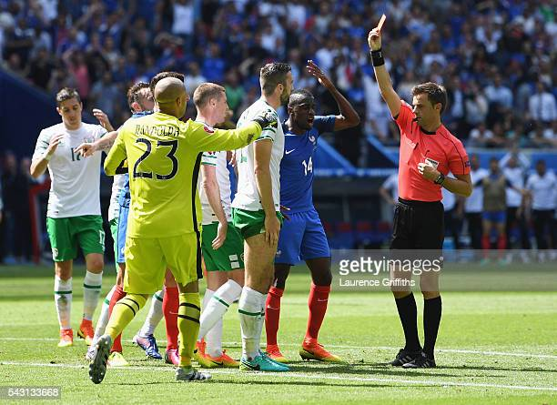 Shane Duffy of Republic of Ireland is shown a red card by referee Nicola Rizzoli during the UEFA EURO 2016 round of 16 match between France and...