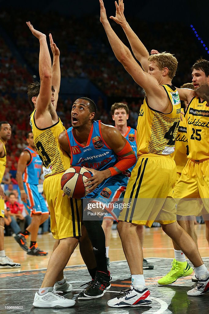 Shane Edwards of the Taipans looks to layup against <a gi-track='captionPersonalityLinkClicked' href=/galleries/search?phrase=Damian+Martin+-+Basketball+Player&family=editorial&specificpeople=13687064 ng-click='$event.stopPropagation()'>Damian Martin</a> and Shawn Redhage of the Wildcats during the round 15 NBL match between the Perth Wildcats and the Cairns Taipans at Perth Arena on January 18, 2013 in Perth, Australia.