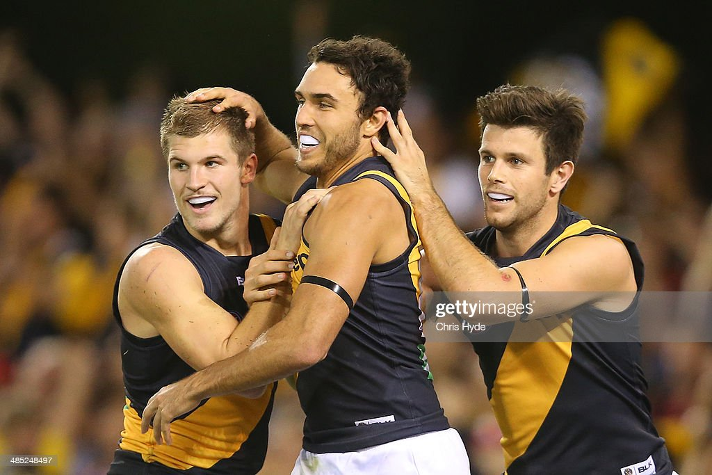 Shane Edwards of the Tigers celebrates with Matt Arnot and Trent Cochin after kicking a goal during the round five AFL match between the Brisbane Lions and the Richmond Tigers at The Gabba on April 17, 2014 in Brisbane, Australia.
