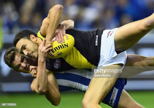 Shane Edwards of the Tigers is tackled by Kayne Turner of the Kangaroos during the round 11 AFL match between the North Melbourne Kangaroos and the...