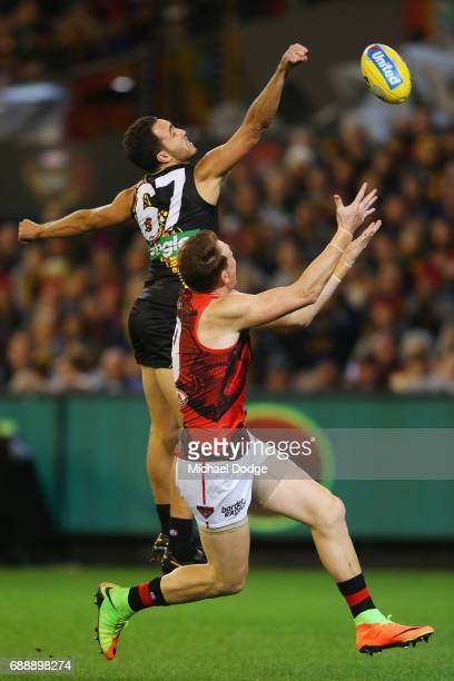 Shane Edwards of the Tigers punches the ball away from Brendon Goddard of the Bombers during the round 10 AFL match between the Richmond Tigers and...