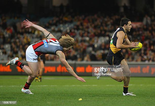 Shane Edwards of the Tigers runs with the ball during the round 22 AFL match between the Richmond Tigers and the Essendon Bombers at the Melbourne...