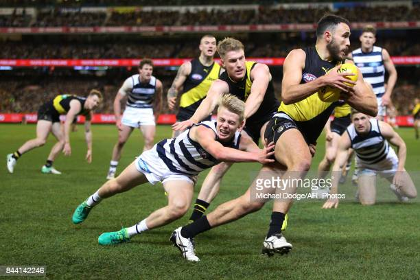 Shane Edwards of the Tigers runs with the ball from Zach Guthrie of the Cats during the AFL Second Qualifying Final Match between the Geelong Cats...