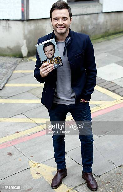 Shane Filan poses for pictures with his book 'My Side of Life the Autobiography by Shane' as he leaves the ITV Studios on October 14 2014 in London...