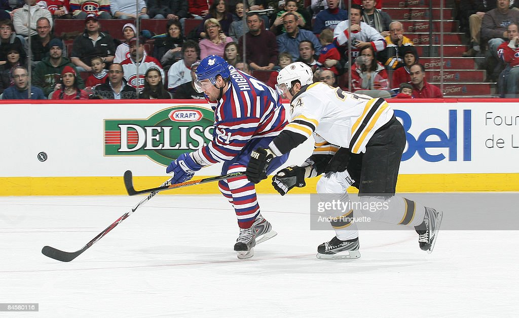 Shane Hnidy of the Boston Bruins stick checks the puck away from Christopher Higgins of the Montreal Canadiens at the Bell Centre on February 1 2009...