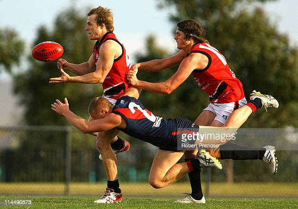 Shane Hockey of Frankston handballs whilst being tackled by Nick Carnell of the Tigers during the round eight VFL match between the Coburg Tigers and...