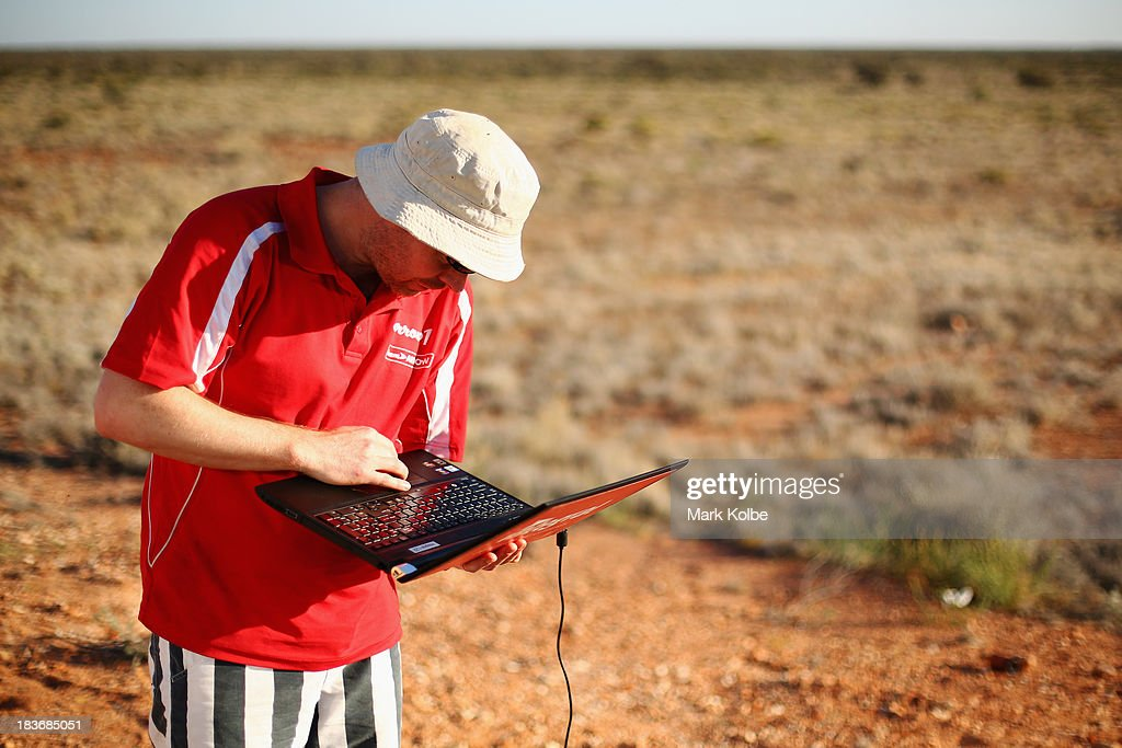 Shane Hughes from Team Arrow, Associated with Queensland University of Technology in Australia works on a laptop as they prepare Arrow1 for racing on Day 4 on October 9, 2013 between Alice Springs and Kulgera, Australia. Over 25 teams from across the globe are competing in the 2013 World Solar Challenge - a 3000 km solar-powered vehicle race between Darwin and Adelaide. The race began on October 6th with the first car expected to cross the finish line on October 10th.