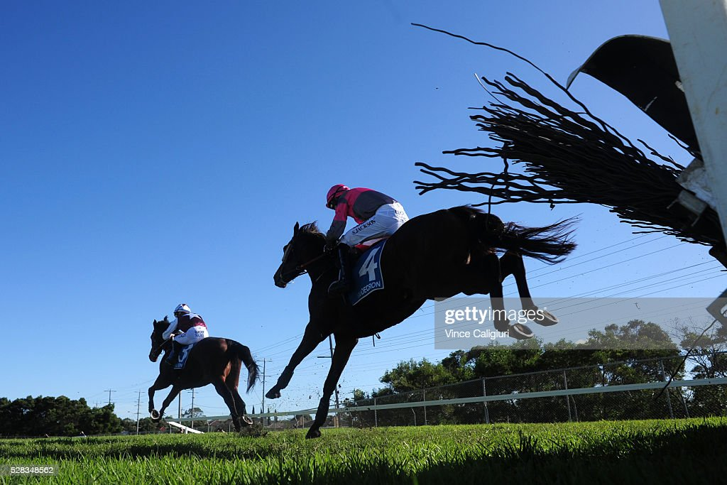 Shane Jackson riding Gold Medals gives chase to <a gi-track='captionPersonalityLinkClicked' href=/galleries/search?phrase=John+Allen+-+Jockey&family=editorial&specificpeople=15787046 ng-click='$event.stopPropagation()'>John Allen</a> riding Twin Tea Bags before winning Race 1 during Grand Annual Day at Warrnambool Race Club on May 5, 2016 in Warrnambool, Australia.