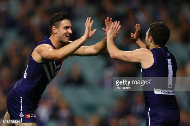 Shane Kersten and Hayden Ballantyne of the Dockers celebrate a goal during the round 20 AFL match between the Fremantle Dockers and the Gold Coast...
