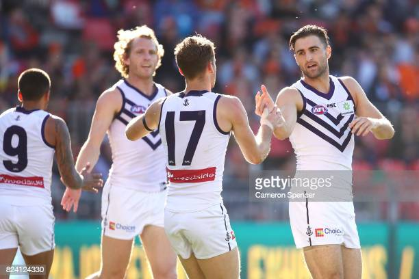 Shane Kersten of the Dockers celebrates kicking a goal with team mates during the round 19 AFL match between the Greater Western Sydney Giants and...