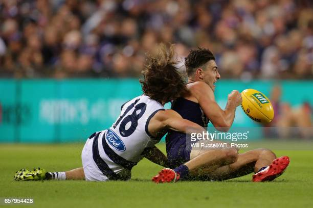 Shane Kersten of the Dockers handballs under pressure from Josh Cowan of the Cats during the round one AFL match between the Fremantle Dockers and...
