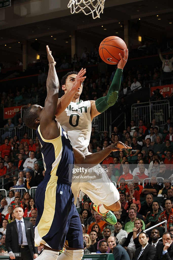 Shane Larkin #0 of the Miami Hurricanes is fouled by Mfon Udofia #0 of the Georgia Tech Yellow Jackets as he goes to the basket on March 6, 2013 at the BankUnited Center in Coral Gables, Florida.