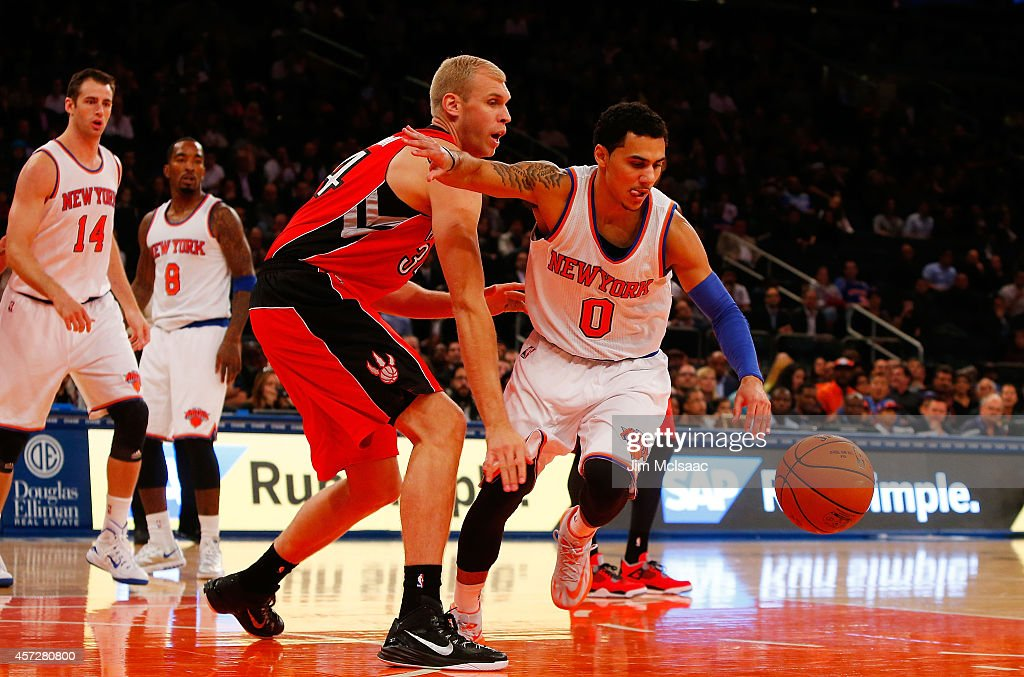Shane Larkin of the New York Knicks in action against Greg Stiemsma of the Toronto Raptors at Madison Square Garden on October 13 2014 in New York...