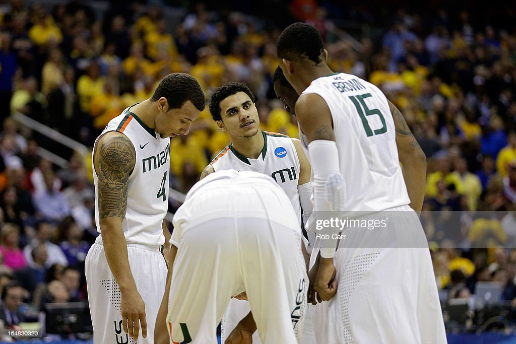 Shane Larkin #0, Trey McKinney Jones #4 and Rion Brown #15 of the Miami (Fl) Hurricanes huddle up against the Marquette Golden Eagles during the East Regional Round of the 2013 NCAA Men's Basketball Tournament at Verizon Center on March 28, 2013 in Washington, DC.